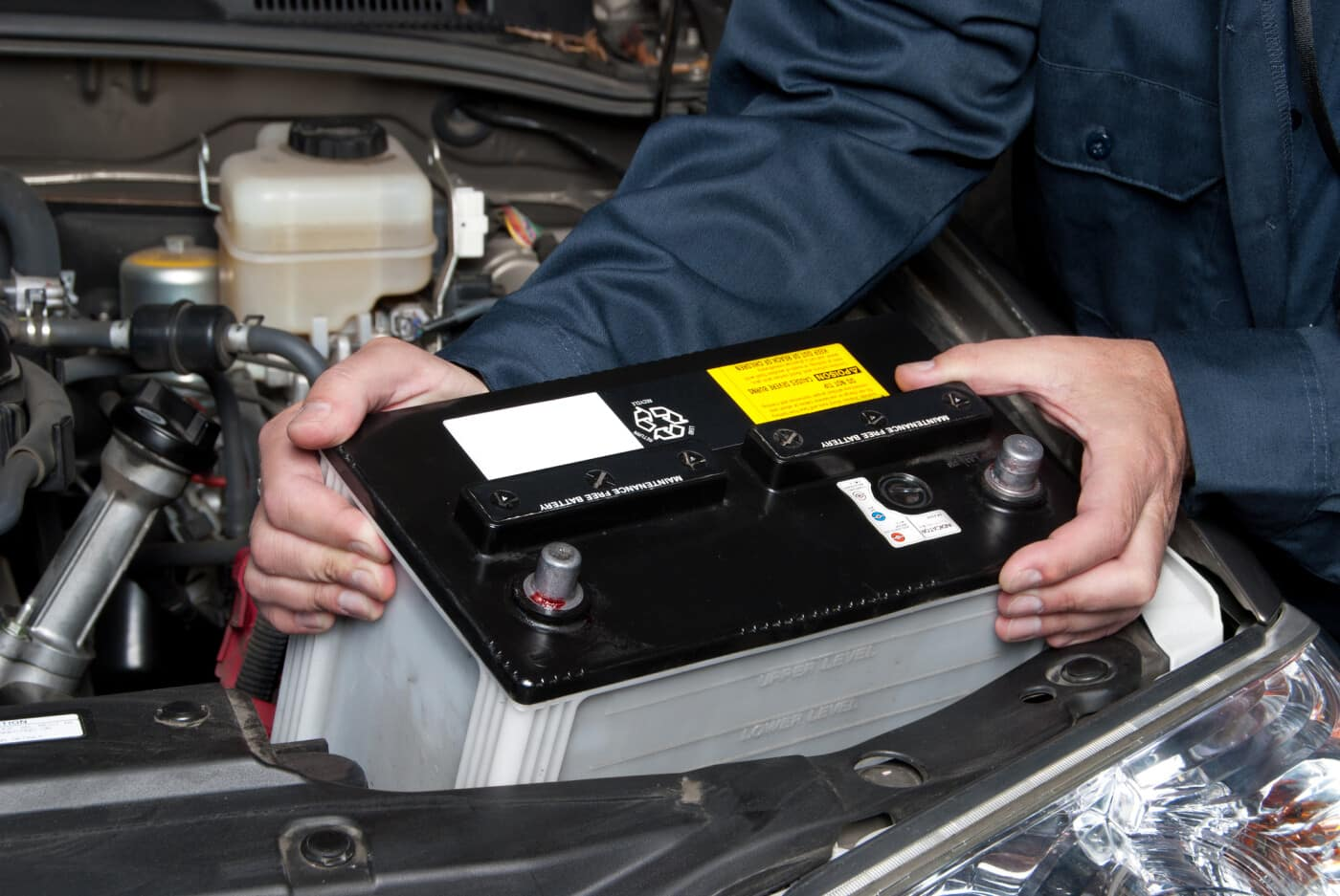 Car mechanic replaces a battery.