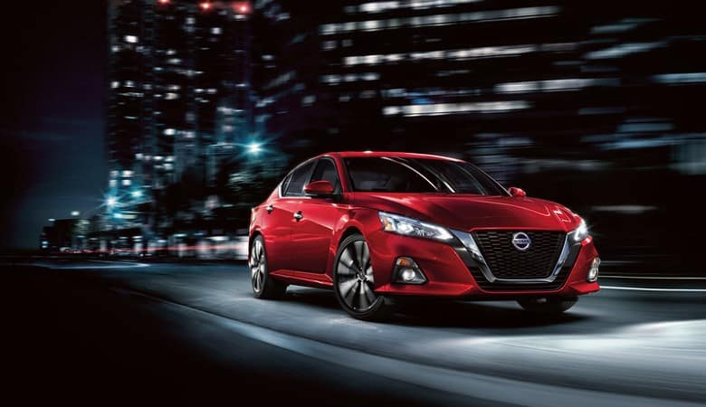 A red 2019 Nissan Altima driving at night in the city - Bert Ogden Nissan in McAllen, TX