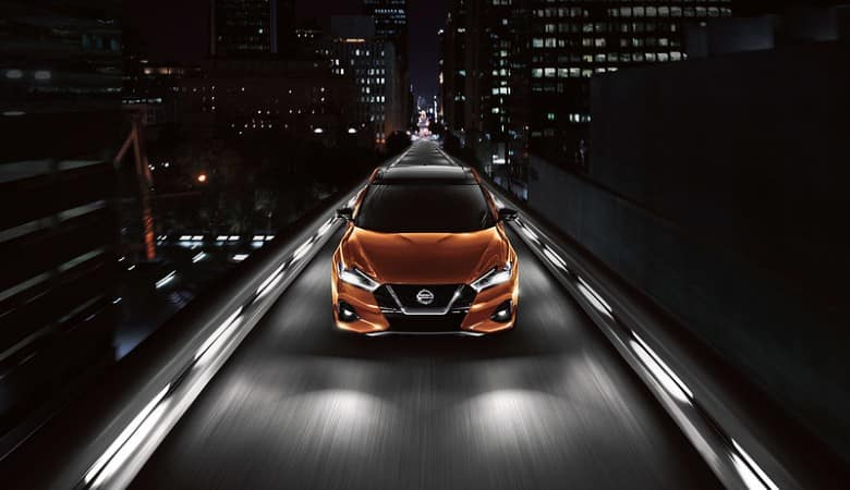 An orange 2020 Nissan Maxima on a city road at night - Bert Ogden Nissan in McAllen, TX