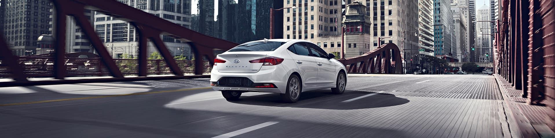 Boch Hyundai is a Luxury Car Dealership near Boston MD | White MY20 Hyundai Elantra driving across city bridge