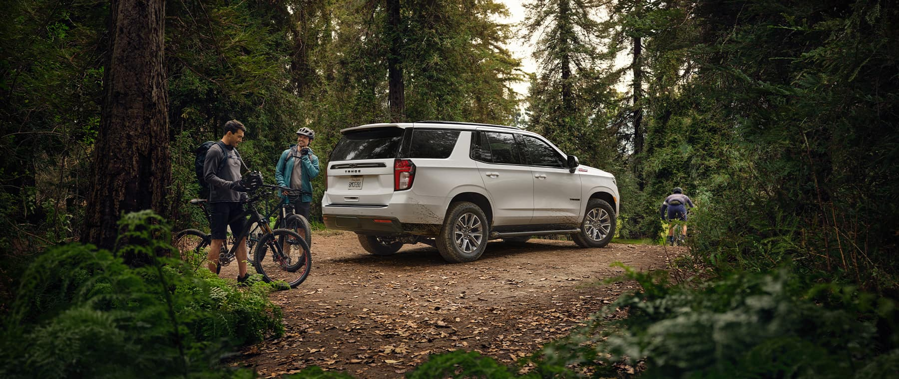 2021 Chevrolet Tahoe in forest with mountain bikers