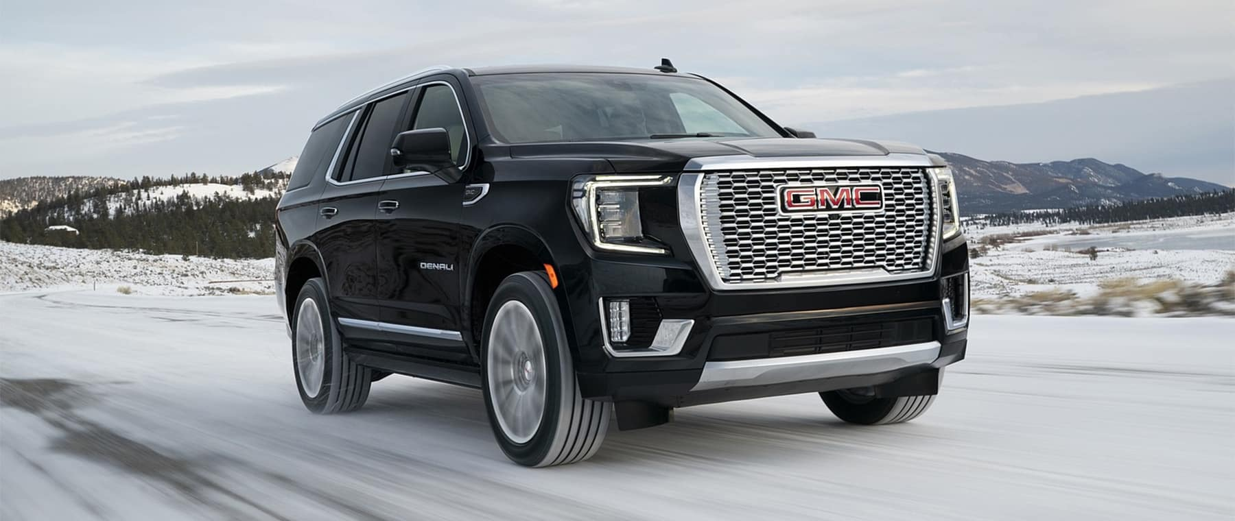 2021 GMC Yukon black driving on snowy road