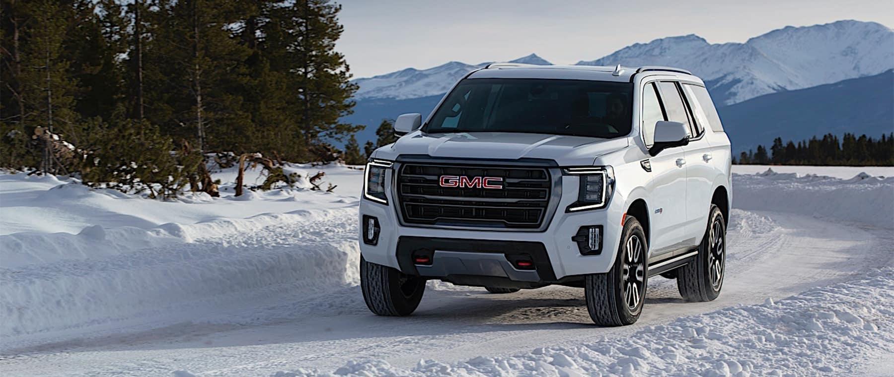 2021 GMC Yukon white driving on snowy path