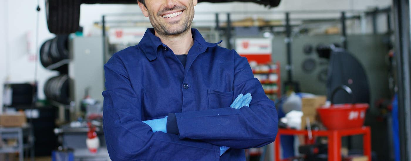 A mechanic is smiling with crossed arms.