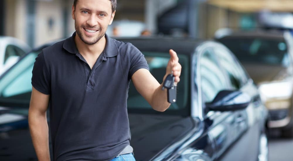 A man is holding the keys to his car that he purchased.