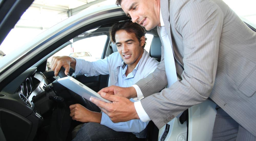 A salesman is going over vehicle information with a customer about used cars in Durham, NC.