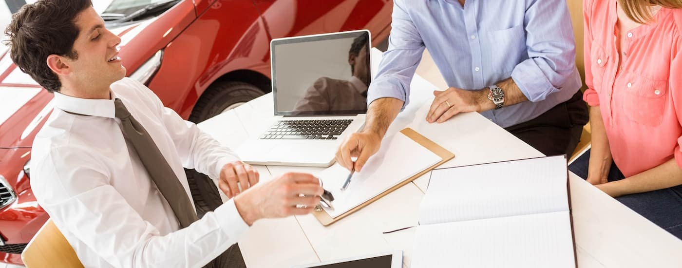 A couple is signing paperwork at a dealership for a car loan.