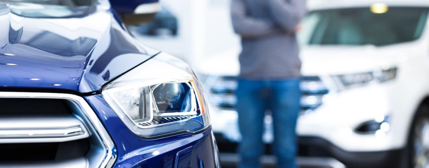 The headlight of a blue car is shown in closeup while a man is looking at it in the distance.