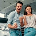 A happy couple is celebrates the great customer service they received in front of their new car.