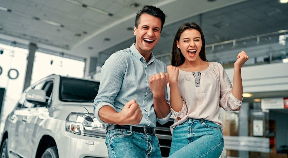 A happy couple is celebrating the great customer service they received in front of their new car.