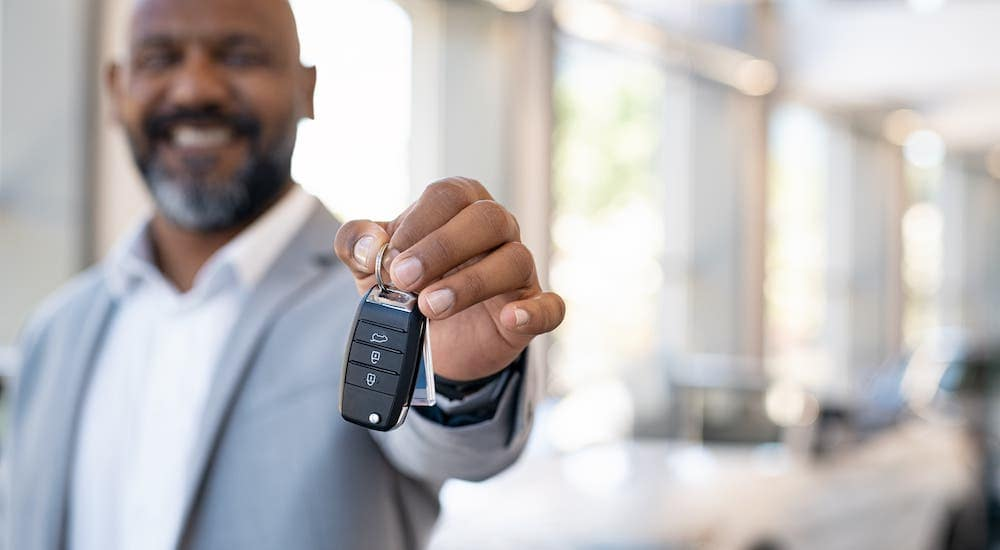 A man is holding car keys in a showroom at a used car dealership near me.