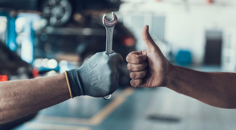 Two hands are in a garage, one with a thumbs up and one with a glove and a wrench.