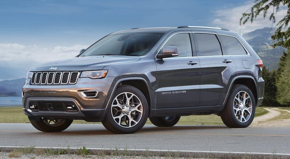 A grey 2018 Jeep Grand Cherokee is parked near a used car dealership near me with mountains in the distance.
