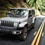 A silver 2019 Jeep Wrangler Unlimited is driving on a road through the woods near Durham, NC.