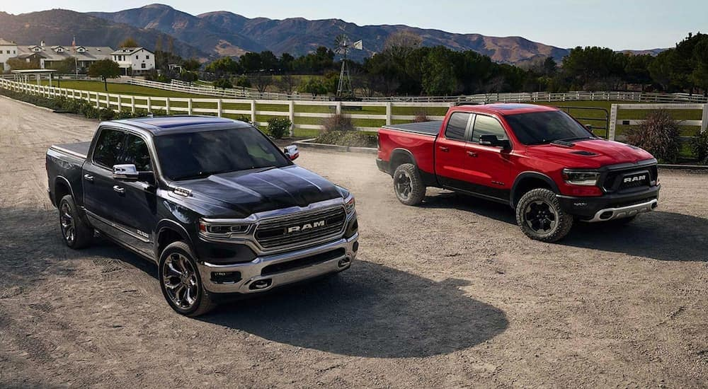A black 2019 Ram 1500 is parked next to a Rebel edition at a farm.