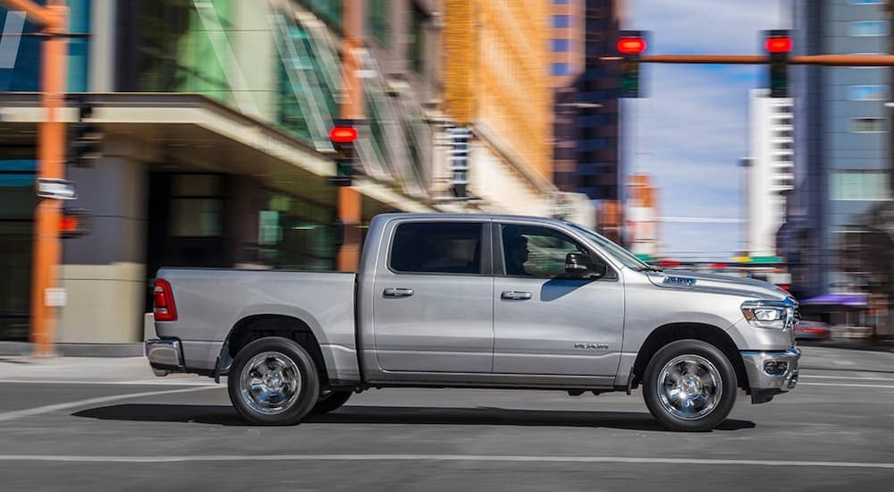 A silver 2019 Ram 1500 is driving through an intersection in Durham, NC, after leaving a used car dealership near me.