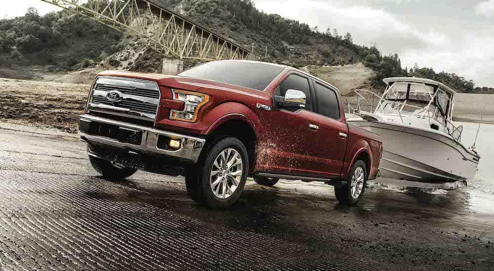 A red 2017 Ford F-150, which is popular among used cars in Durham, NC, is towing a boat out of the water.