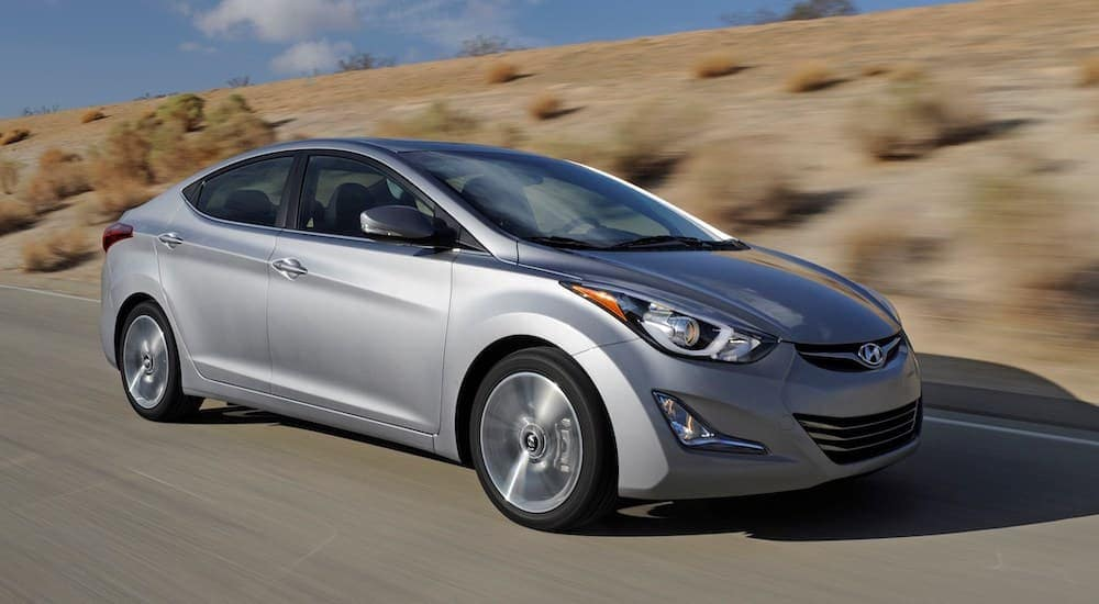 A grey 2014 Hyundai Elantra is driving on a highway outside of Durham, NC, past dirt and shrubs.
