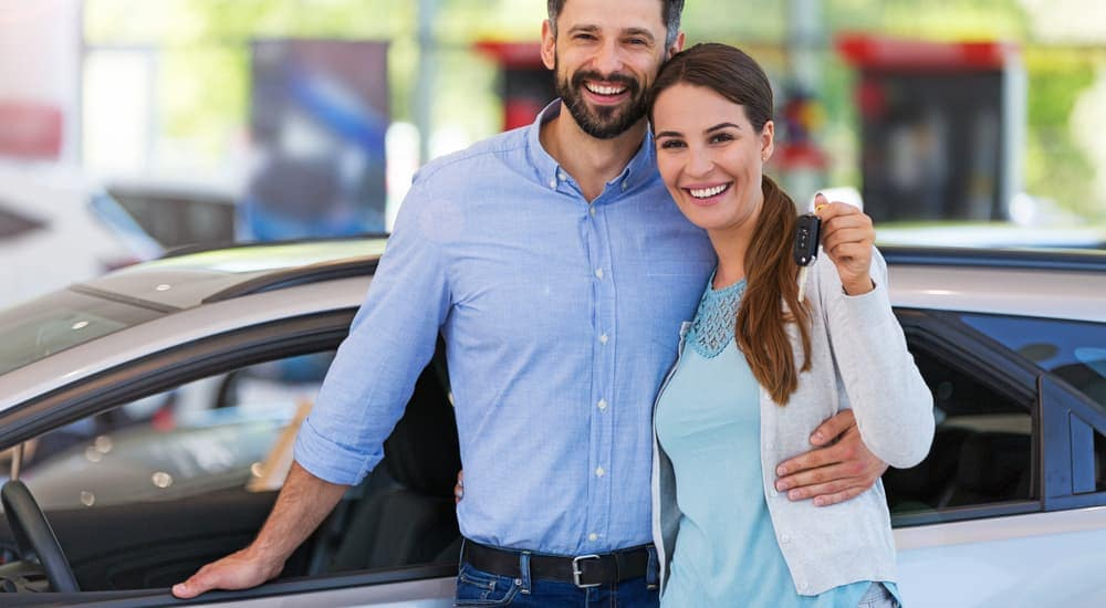 A couple is holding the keys to a car they just bought in Durham, NC.