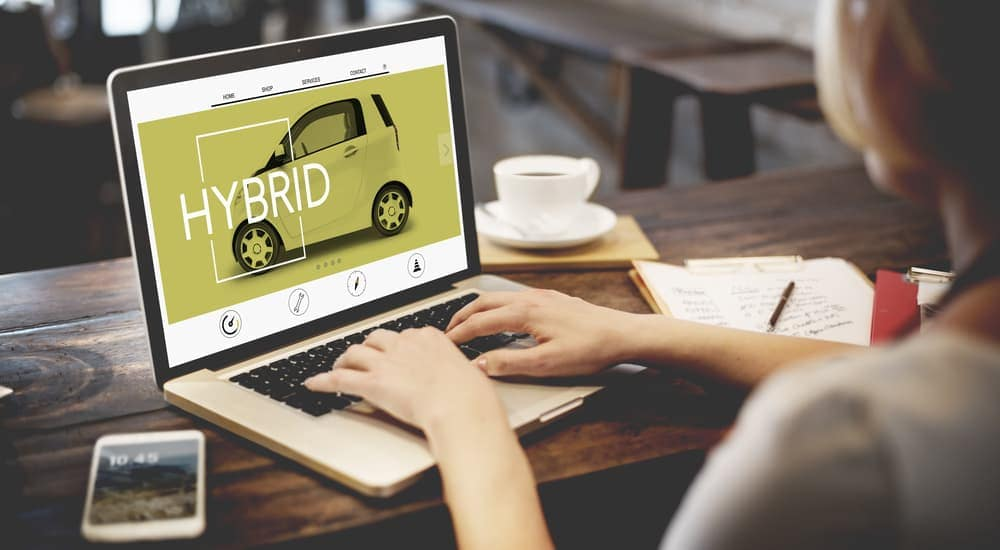 A hybrid car is displayed on a laptop screen.