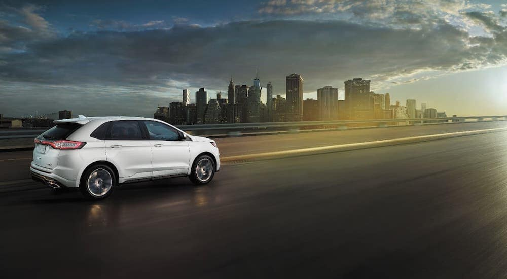 A white 2017 Ford Edge is driving on a highway towards a distant city.