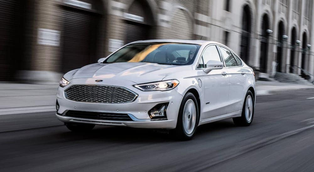 A white 2019 Ford Fusion is driving on a city street after leaving a used car dealership near you.