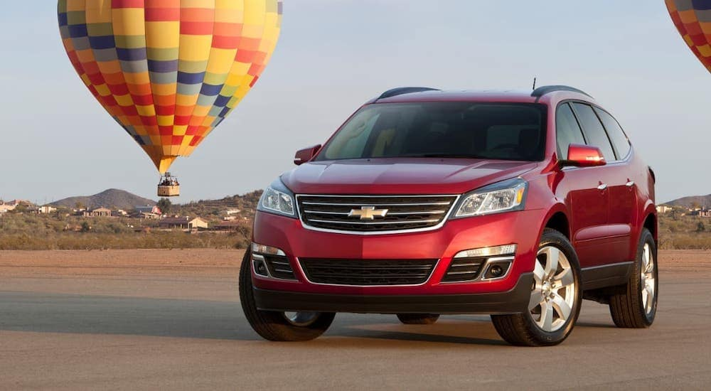 A red 2016 Chevy Traverse LTZ is parked in font of hot air balloons near Durham, NC.