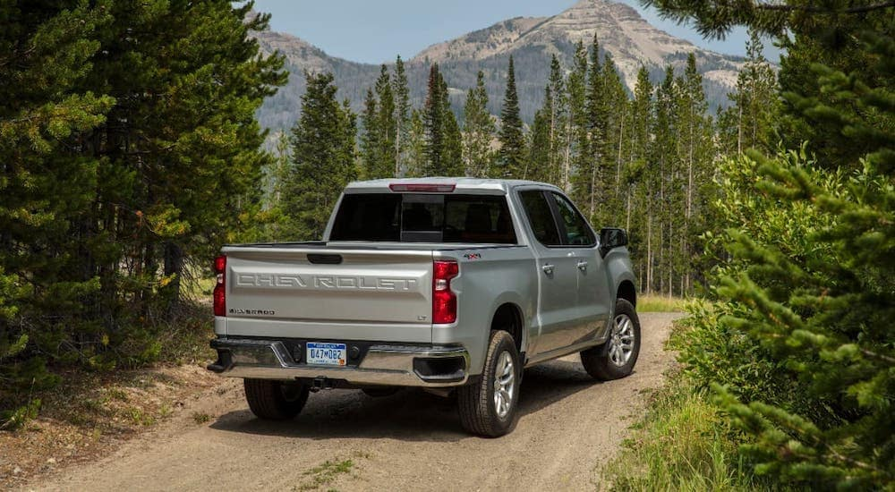 A silver 2019 Chevy Silverado 1500 LT is driving on dirt trail towards a mountain.