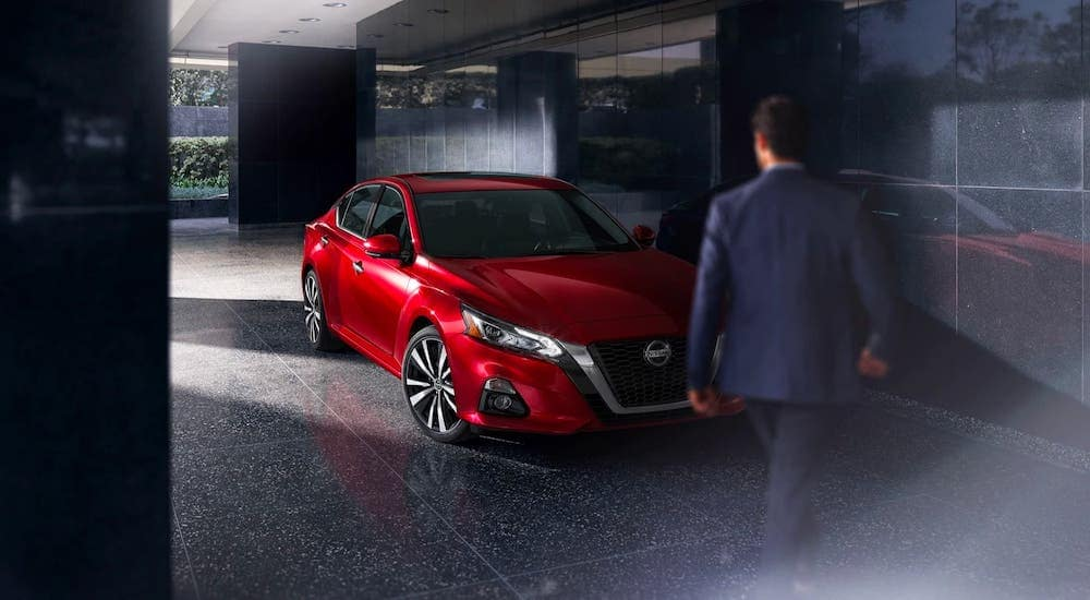 A man is walking towards a red 2019 Nissan Altima