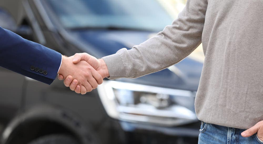 A salesman is shaking hands with a man in front of a black car at a used car dealership near me.