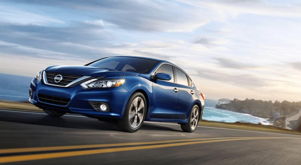 A blue 2018 Nissan Altima, which is popular among used cars near me, is driving past an ocean bay.
