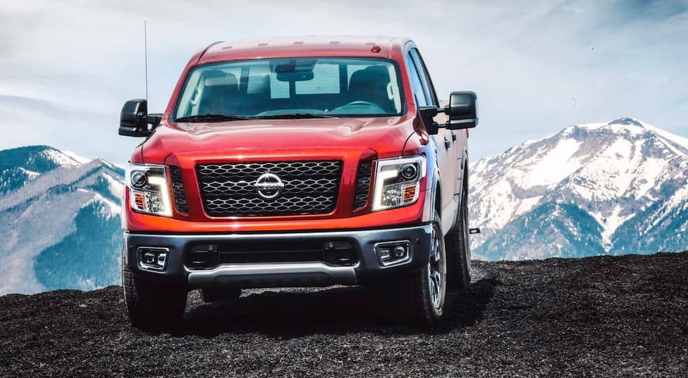 A red 2018 Nissan Titan is parked in front of snowy mountains.