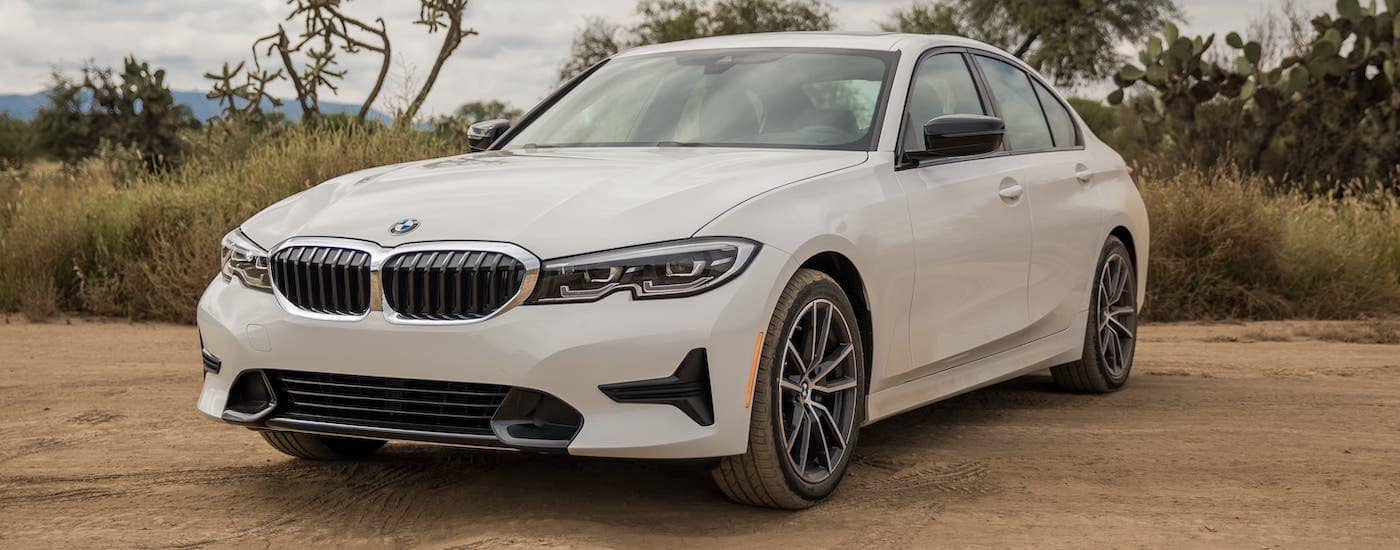 One of the used cars near you, a white 2019 BMW 3 Series, is parked on a dirt road.