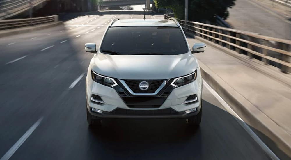 A white 2020 Nissan Rogue Sport is driving on a city highway near Durham, NC.