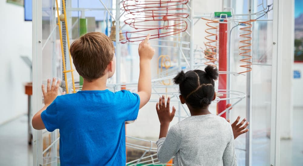 Two kids are playing with an exhibit at a museum.