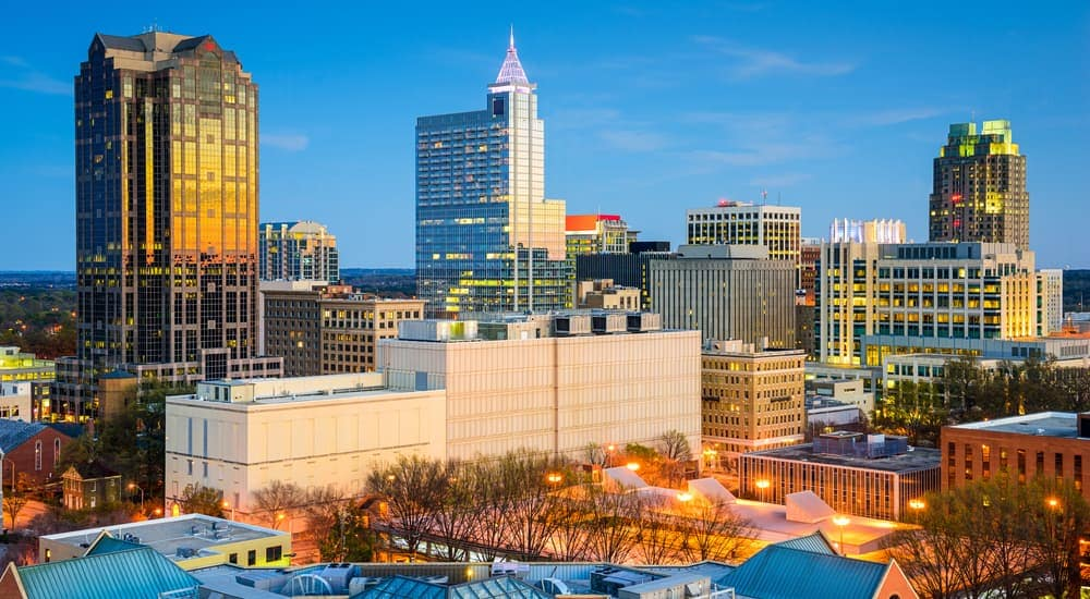 The Raleigh, NC, skyline is shown in front of a blue sky.