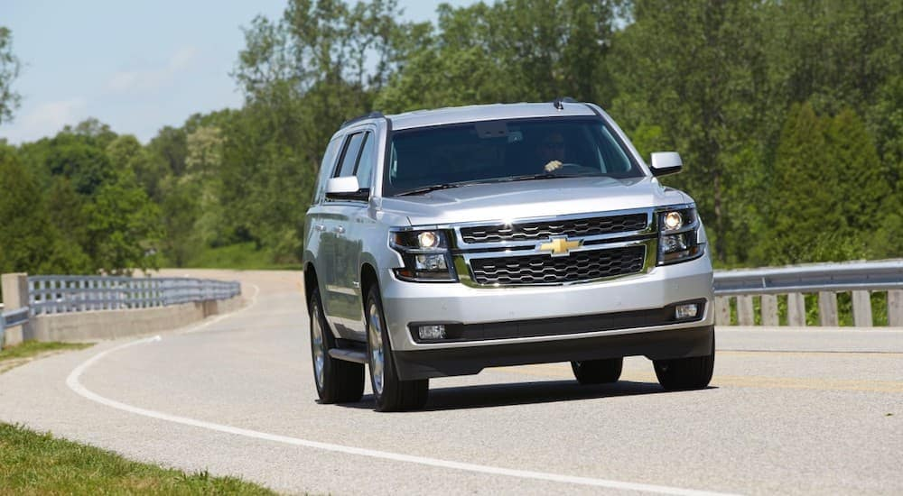 A 2015 Chevy Suburban is driving on a winding road past trees.