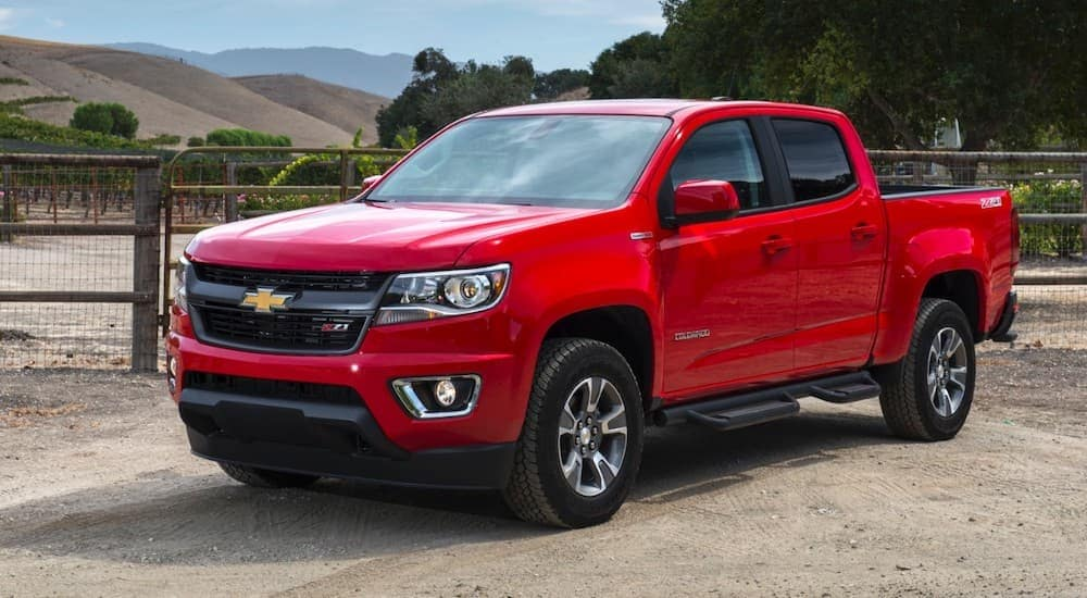 A red 2017 Chevy Colorado, which is popular among used cars near me, is parked in front of a fence with hills in the distance.