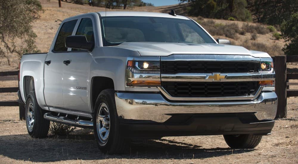 A silver 2017 Chevy Silverado is parked in front of a fence and dry grass near Durham, NC.