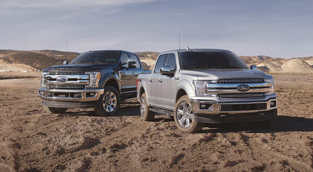 A black 2018 Ford F-250 is parked behind a silver 2018 F-150 on dirt with hills in the distance.