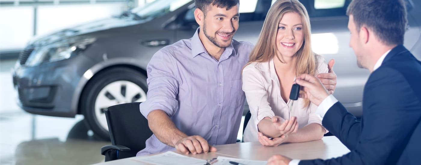 A salesman is handing a couple keys at a used car dealership.