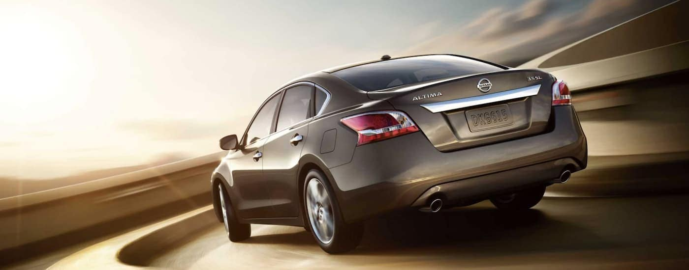 A grey 2013 Used Nissan Altima is shown from the rear driving around a corner in bright sun.