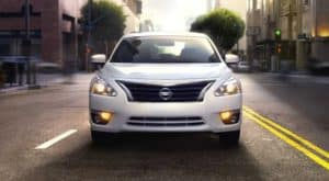A white 2014 Used Nissan Altima is shown from the front on a city street.