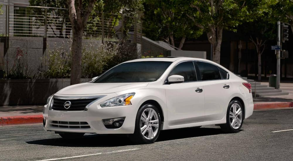 A white 2015 used Nissan Altima is shown from the front parked on the street angled left.