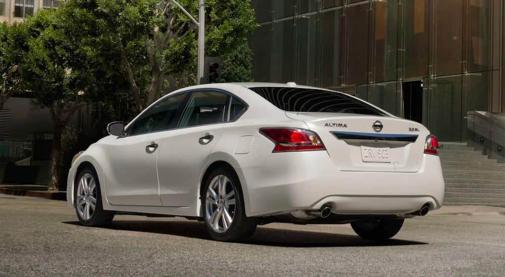 A white 2015 used Nissan Altima is shown from the back parked on the street.