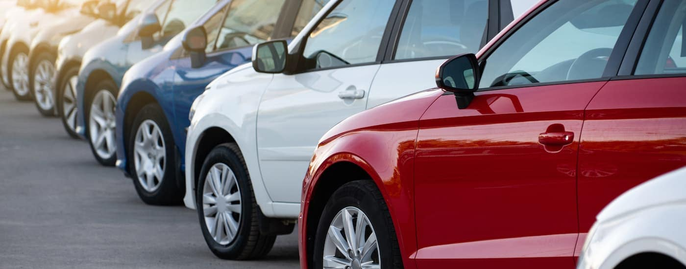 Cars are shown in a row at a dealership.
