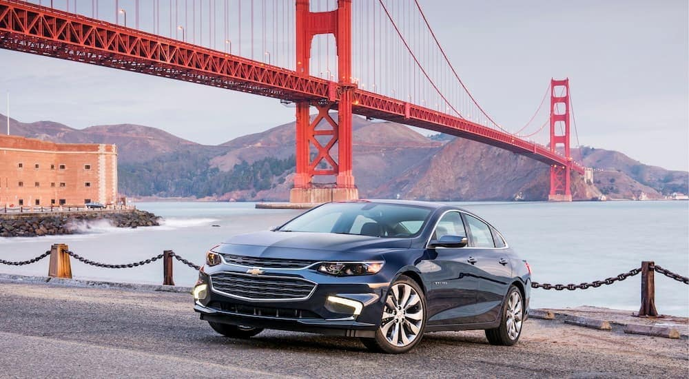 A blue 2018 Chevy Malibu is parked at the pier with a red bridge in the background.