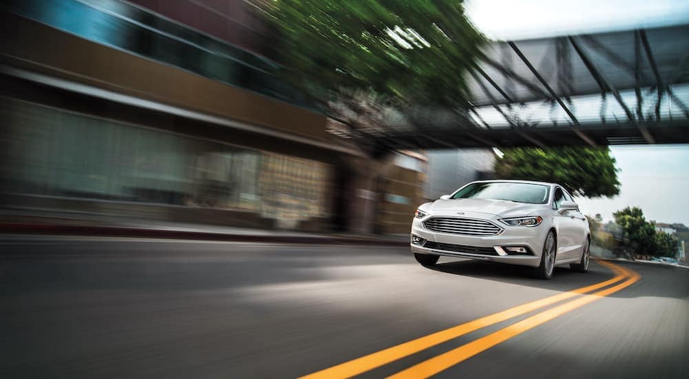A white 2018 Ford Fusion, a popular used car in Durham, NC, is driving past blurred buildings.