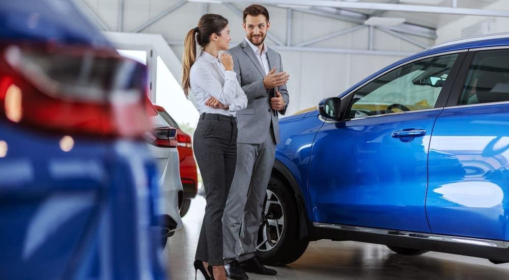 A salesman is showing a woman blue cars at a car dealership in Durham, NC.