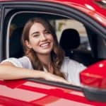 A woman is smiling inside a red car.